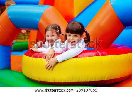 happy kids, girls having fun on inflatable attraction playground - stock photo