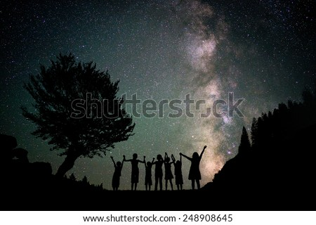 Happy kids group silhouette with Milky Way and beautiful night sky full of stars in background - stock photo