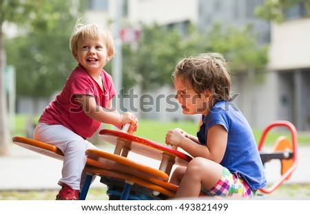 Happy kids having fun at playground in sunny day