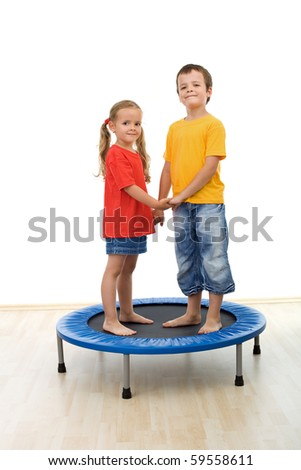 Happy kids having fun in the gym playing on a trampoline - isolated - stock photo