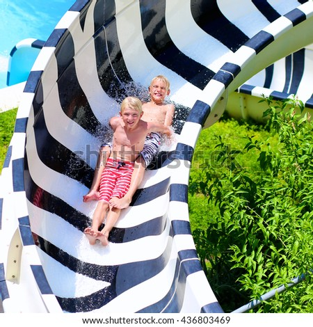 Happy kids having fun in water amusement park. Two teenage boys, sportive twin brothers, jumping and splashing in outdoors swimming pool in aquapark during summer sea vacation - stock photo