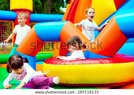 happy kids, having fun on inflatable attraction playground - stock photo