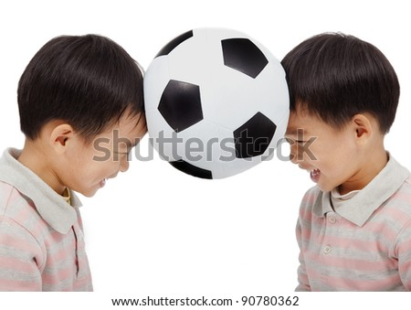happy kids holding a football above their  head - stock photo