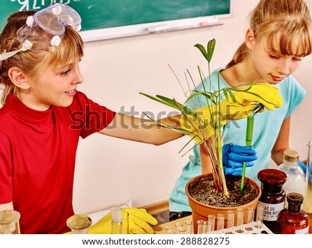 Happy kids holding flask in biology class. - stock photo