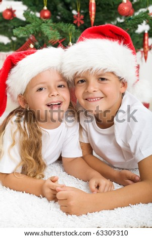 Happy kids in front of christmas tree laughing joyfully - stock photo