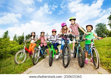 Happy kids in row wear colorful bike helmets - stock photo