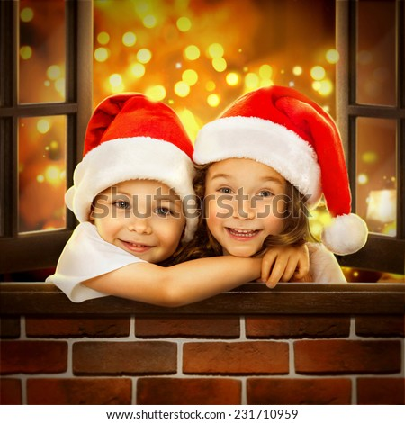 Happy kids in Santa hat  look out  window at Christmas time. With colorful lights from Christmas tree on background. Holidays, christmas, new year, x-mas concept. - stock photo