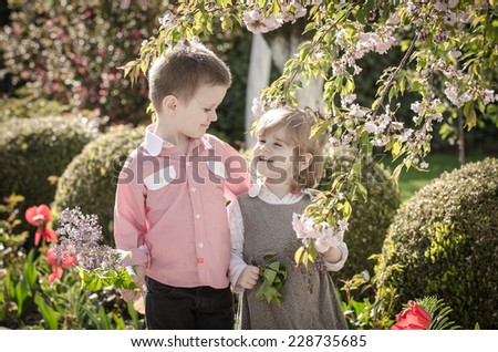 Happy kids in  spring flower garden  - stock photo