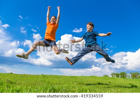 Happy kids jumping on green hills against blue sky