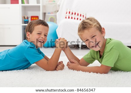 Happy kids laughing and arm wrestling - focus on the left boy - stock photo