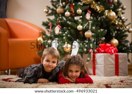 Happy kids laying on the floor in front of the christmas tree and smiling