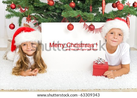 Happy kids laying under the christmas tree with a white banner for text - stock photo