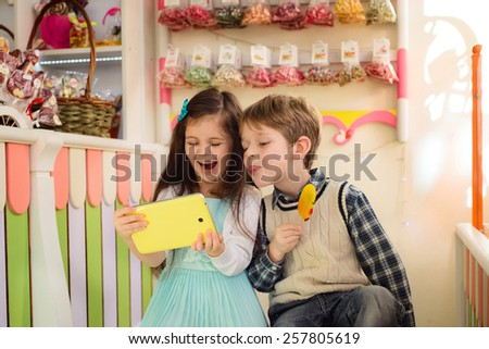Happy kids looking at the tablet. Boy shows tongue holding candy in the hands - stock photo