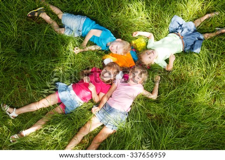 Happy kids lying on grass - stock photo
