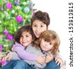 Happy kids near Christmas tree, three little friends enjoying New Year party, Christmastime holidays, best friends, happiness concept - stock photo