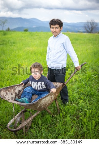 Happy kids on field playing with cart - stock photo