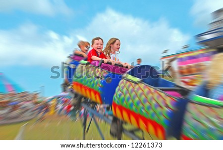 Happy kids on rollercoaster at amusement park - stock photo
