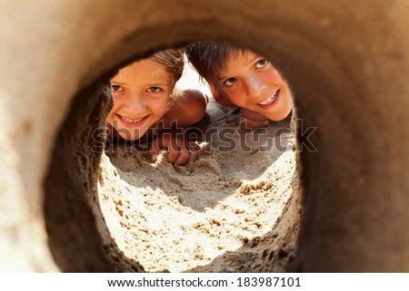 Happy kids on the beach looking through sand castle tunnel and laughing - closeup - stock photo