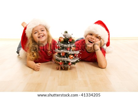 Happy kids on the floor at christmas time with a small decorated tree - isolated - stock photo