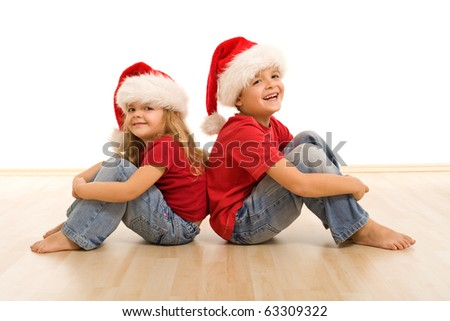 Happy kids on the floor wearing christmas hats, laughing and having fun - isolated - stock photo