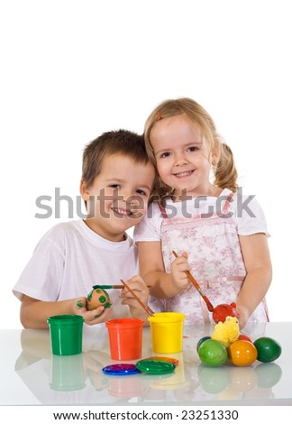 Happy kids painting the easter eggs together - isolated