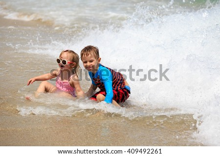 happy kids play with waves on beach
