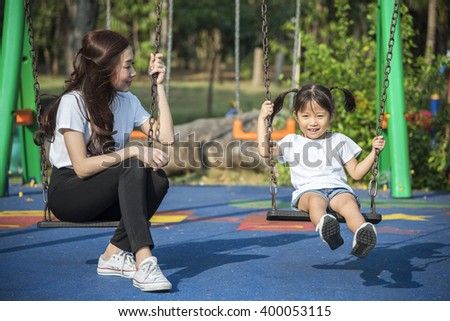 happy kids playing a swing with her mother in a park - stock photo
