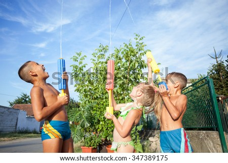 Happy kids playing and splashing with water sprinkler on summer  - stock photo