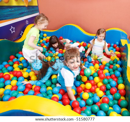 Happy kids playing in the colorful balls - stock photo