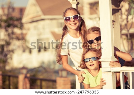 happy kids playing near the house at the day time. They sit in the white gazebo. Concept of friendly family. - stock photo
