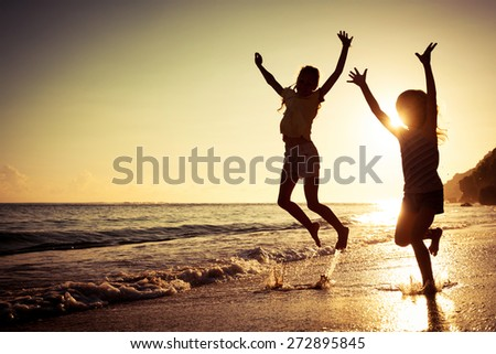 happy kids playing on beach at the sunrise time - stock photo