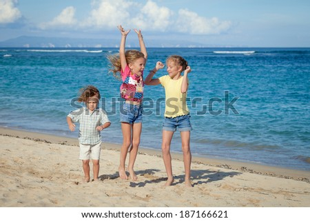 happy kids playing on beach in the day time - stock photo