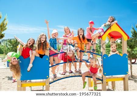 Happy kids playing on playground - stock photo