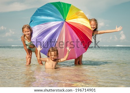 Happy kids playing on the beach at the day time - stock photo