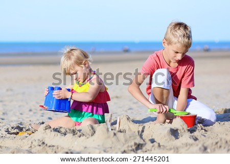 Happy kids playing on the beach. Two adorable children, teenage boy with his toddler sister enjoying summer vacation day building sand castles on the beach. - stock photo
