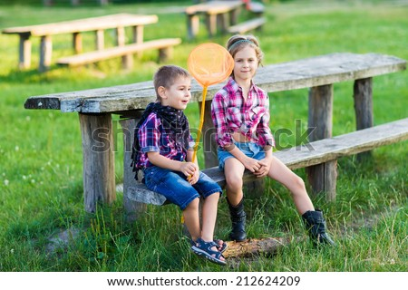 Happy kids playing on the ranch. Western style - stock photo