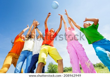 Happy kids playing with ball jumping in air - stock photo