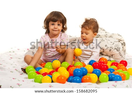 Happy kids playing with many balls in bed - stock photo
