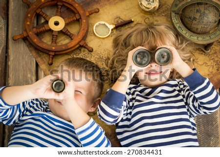 Happy kids playing with nautical things. Children having fun at home. Travel and adventure concept. Unusual high angle view portrait - stock photo