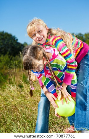 Happy kids playing with the ball in park - stock photo