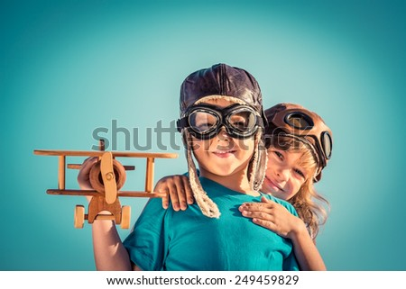 Happy kids playing with vintage wooden airplane outdoors. Portrait of children against summer sky background. Travel and freedom concept. Retro toned - stock photo
