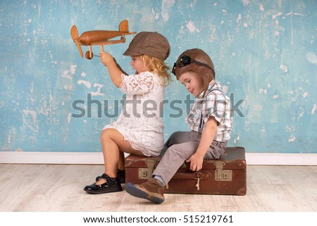 Happy kids playing with vintage wooden airplane. Travel and freedom concept.
