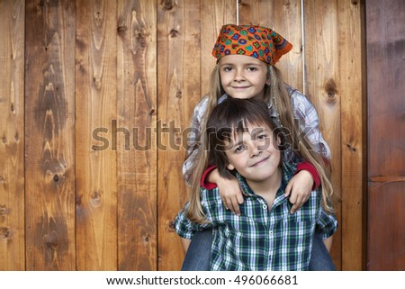 Happy kids portrait against wooden wall - playing in the wood shed, with copy space