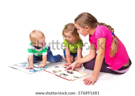 Happy kids reading a book isolated on white. Team work,early education concept.