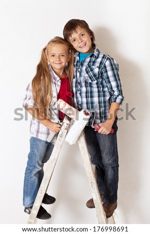 Happy kids ready to paint their room - standing on old wooden ladder - stock photo