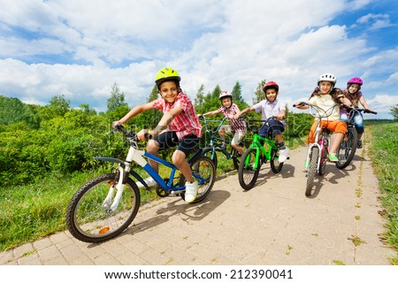 Happy kids riding bikes like in race together - stock photo