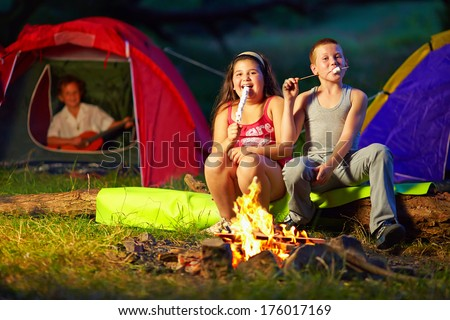 happy kids roasting marshmallows around campfire - stock photo