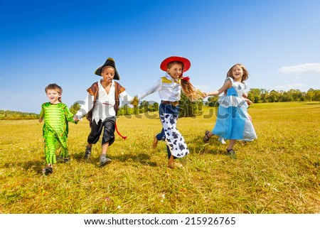 Happy kids run wearing costumes in park - stock photo