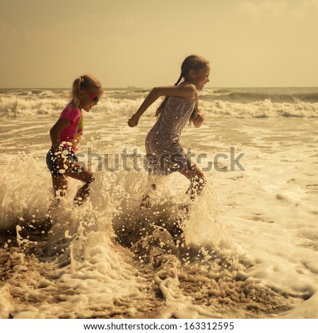 Happy kids running at the beach in the day time - stock photo