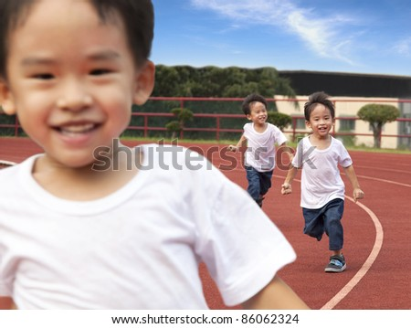 happy kids running on the Stadium track - stock photo